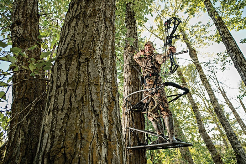 hunter with a bow in a tree stand