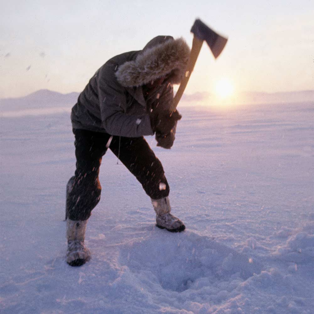 man chopping ice with an axe