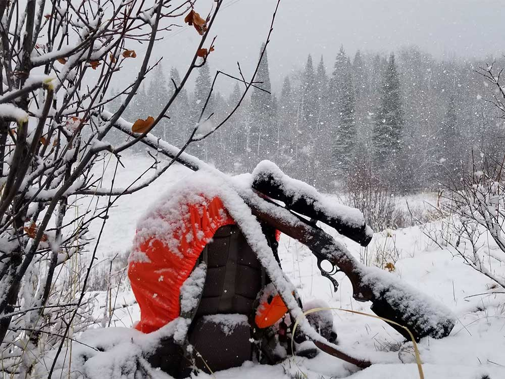 a gun and backpack covered in snow