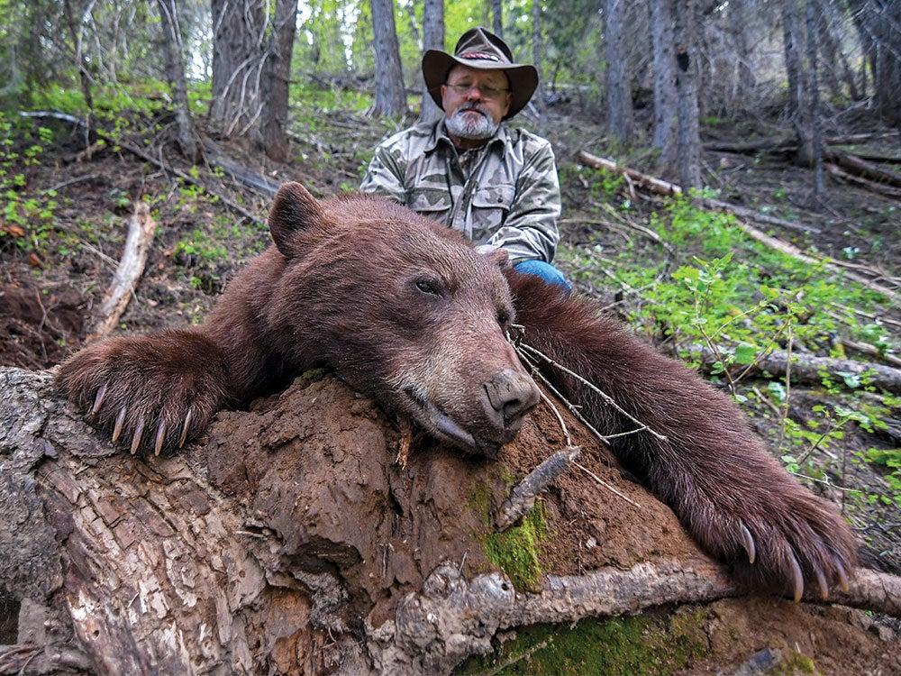older man kneeling behind a bruin bear