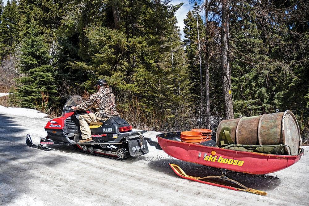 man driving a snowmobile wish supplies in a trailer