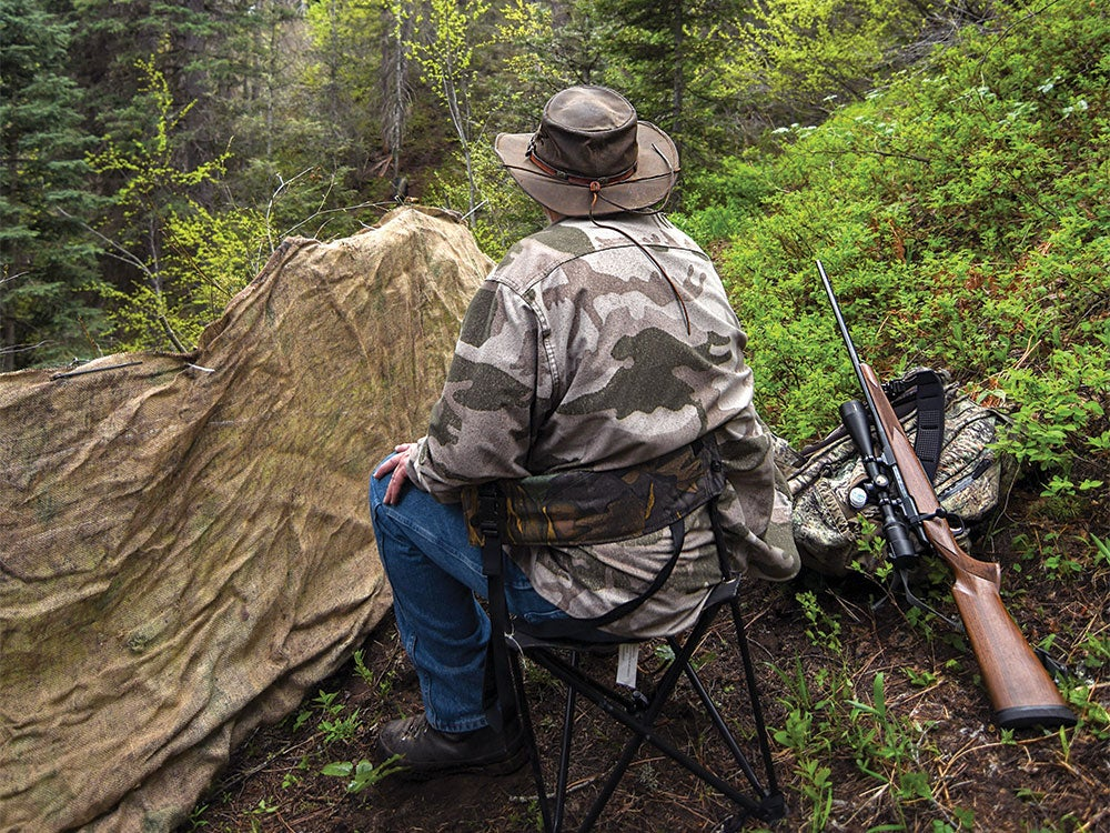 a hunter sitting in a chair overlooking a bear hunt