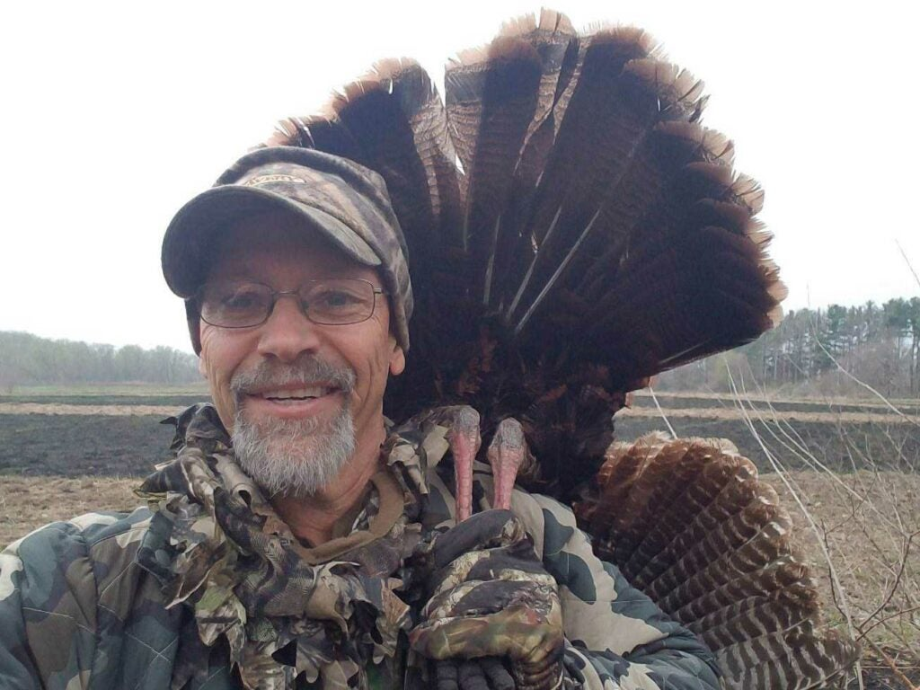 phil bourjaily holding a turkey over his shoulder