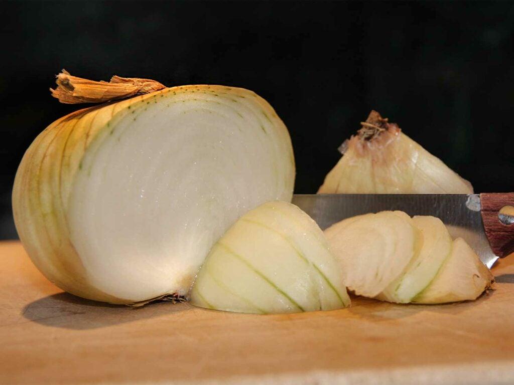 a sliced onion on a wooden cutting board