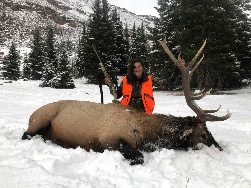 natalie krebs kneeling behind a bull elk