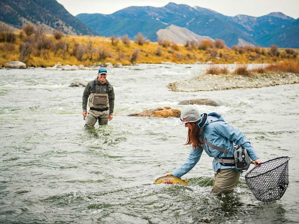 a woman holding a net pulls a brown trout from the river