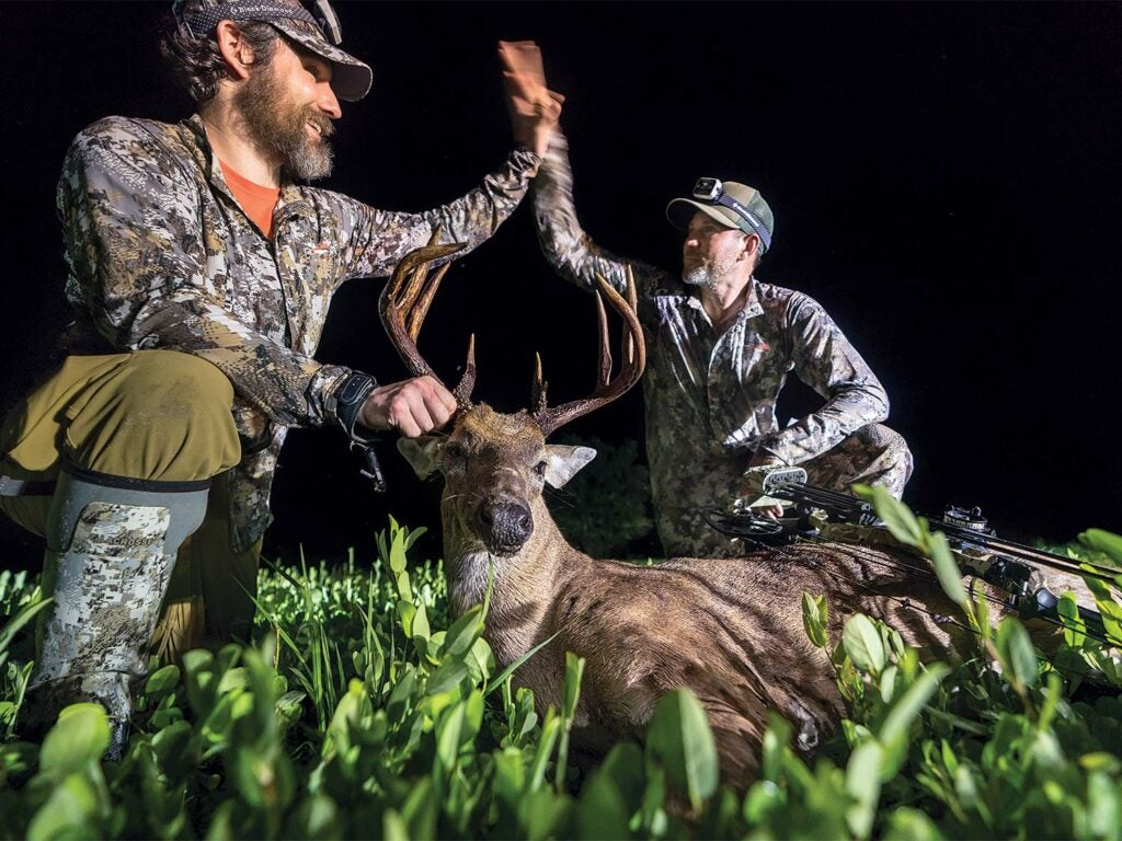 two hunters kneeling over a Florida whitetail buck
