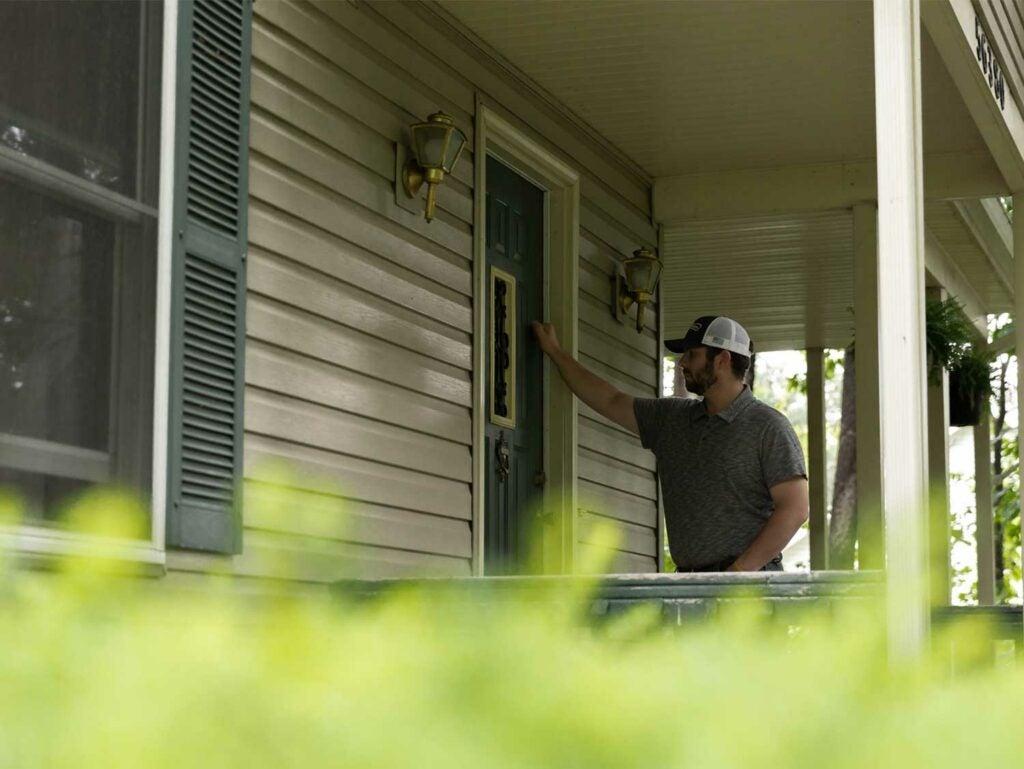 man knocking on front door