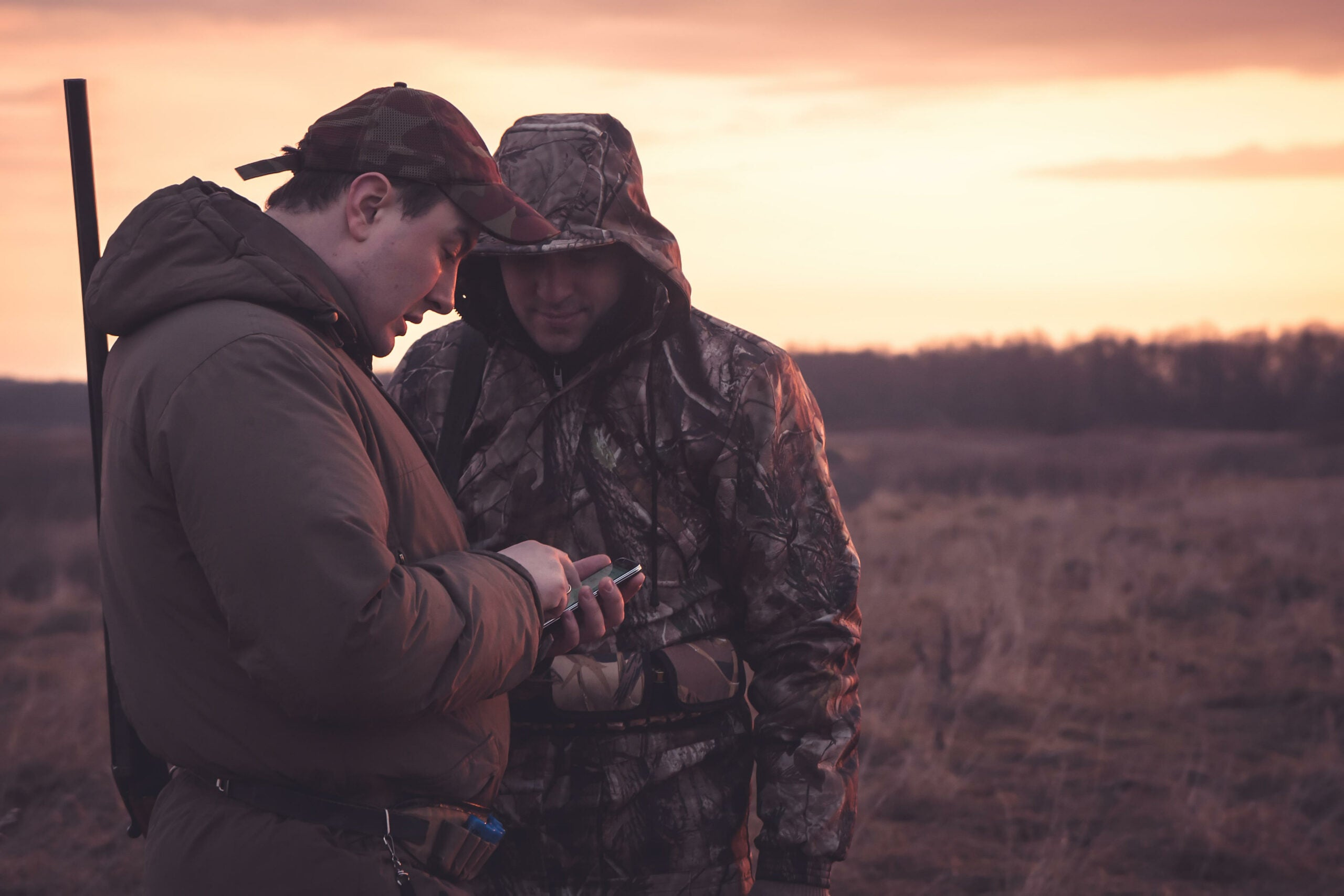 Hunters spot their position via mobile phone  in rural field during hunting season