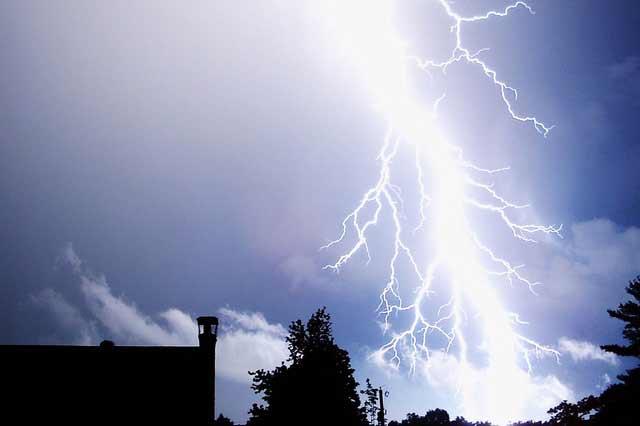 a large bolt of lightning across a blue sky