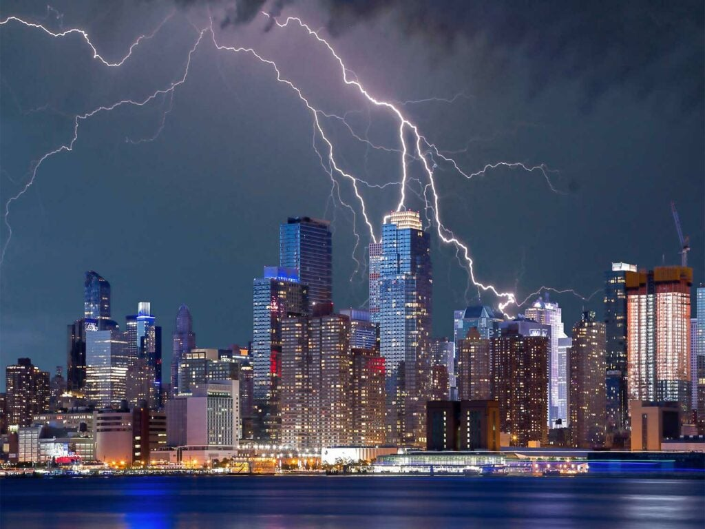 a landscape of the city with a lightning storm