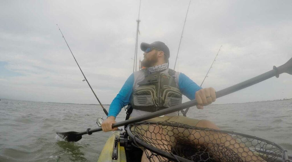 Checking rod tips while trolling for striped bass from a fishing kayak.