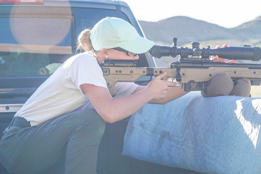 woman aiming rifle in truck bed