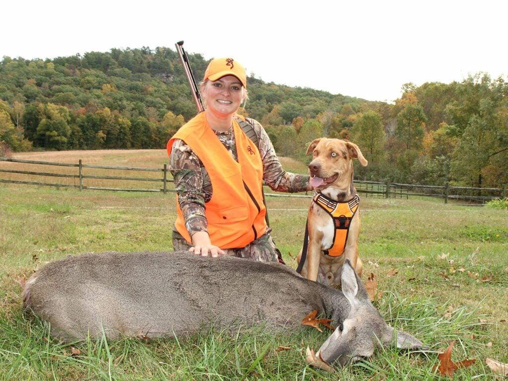 female hunter kneeling by blood-tracking dog and doe