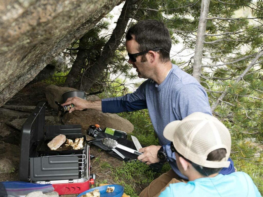 man cooking on outdoor camp grill