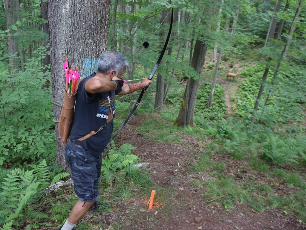 man aiming a bow and arrow in a forest