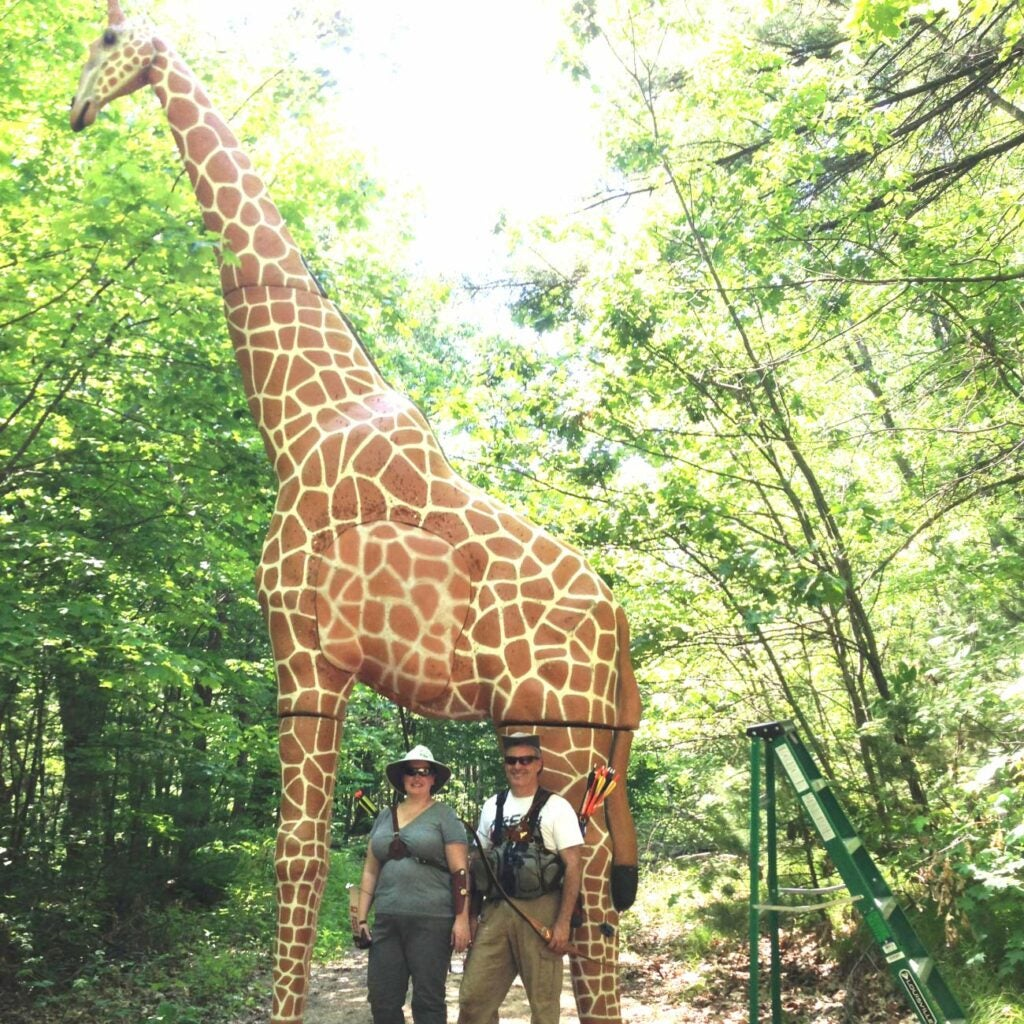 two archers standing in front of a large 3d giraffe archery target