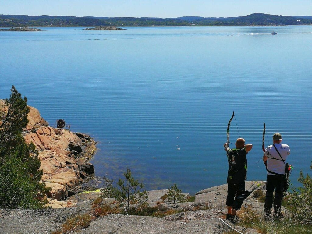 two archers aiming bows above a lake