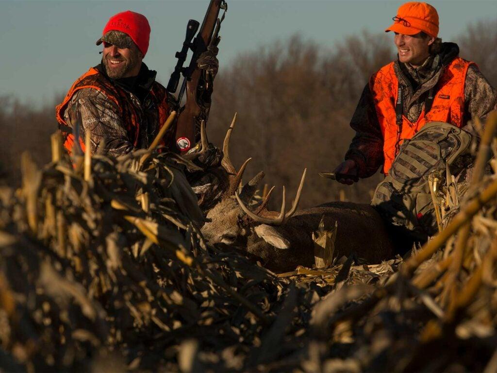 two hunters kneeling over a deer in a corn field