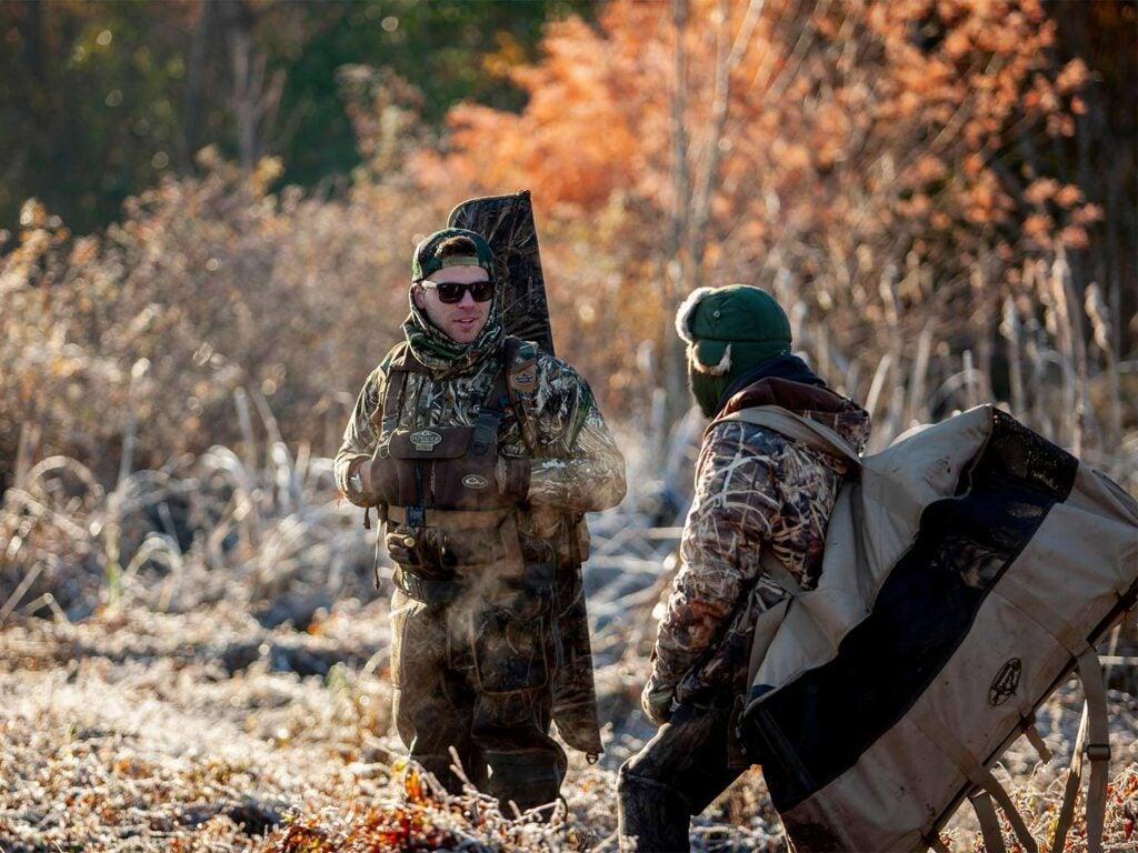 two hunters hauling hunting gear
