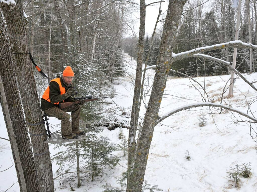 hunter in a tree stand looking over a snowy area