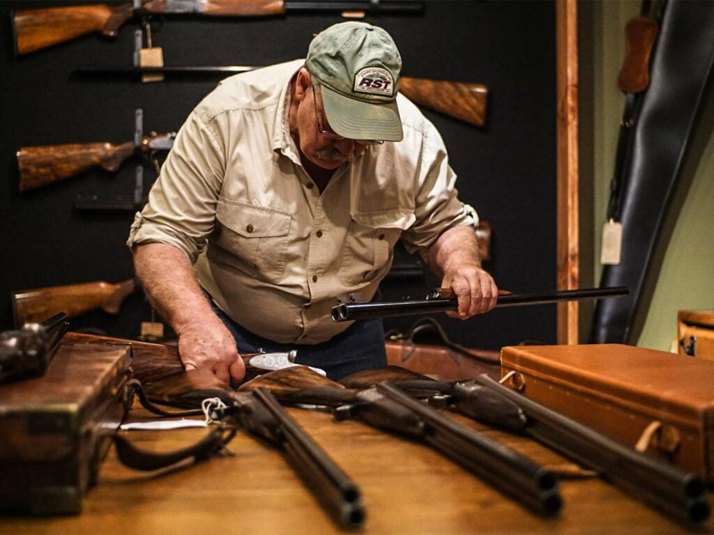 gunsmith inspecting shotgun pieces