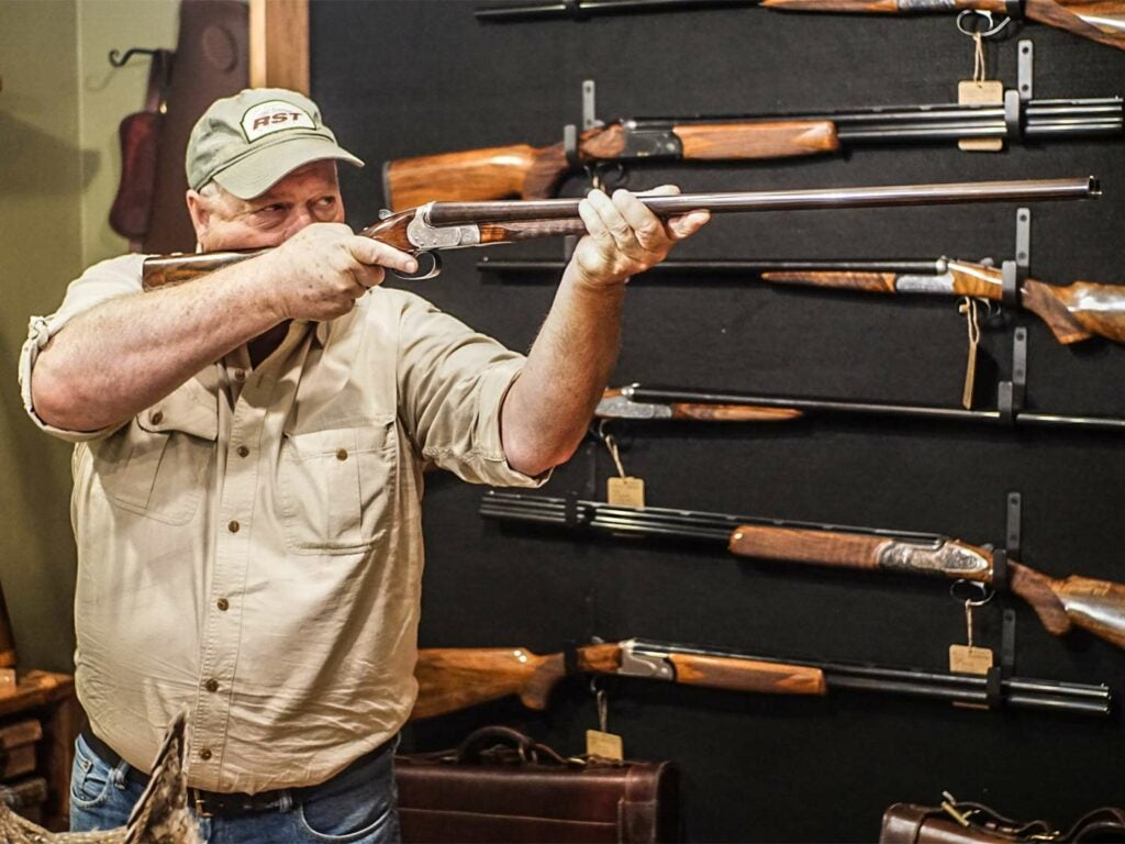 man holding shotgun in gun store