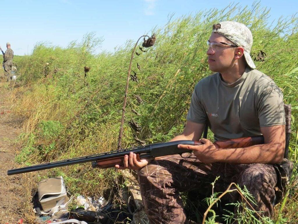 young male hunter holding a shotgun