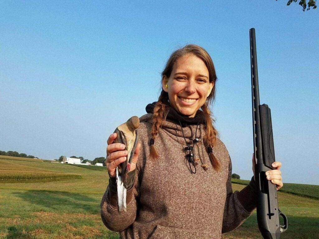 a female hunter holding a dove and a remington shotgun