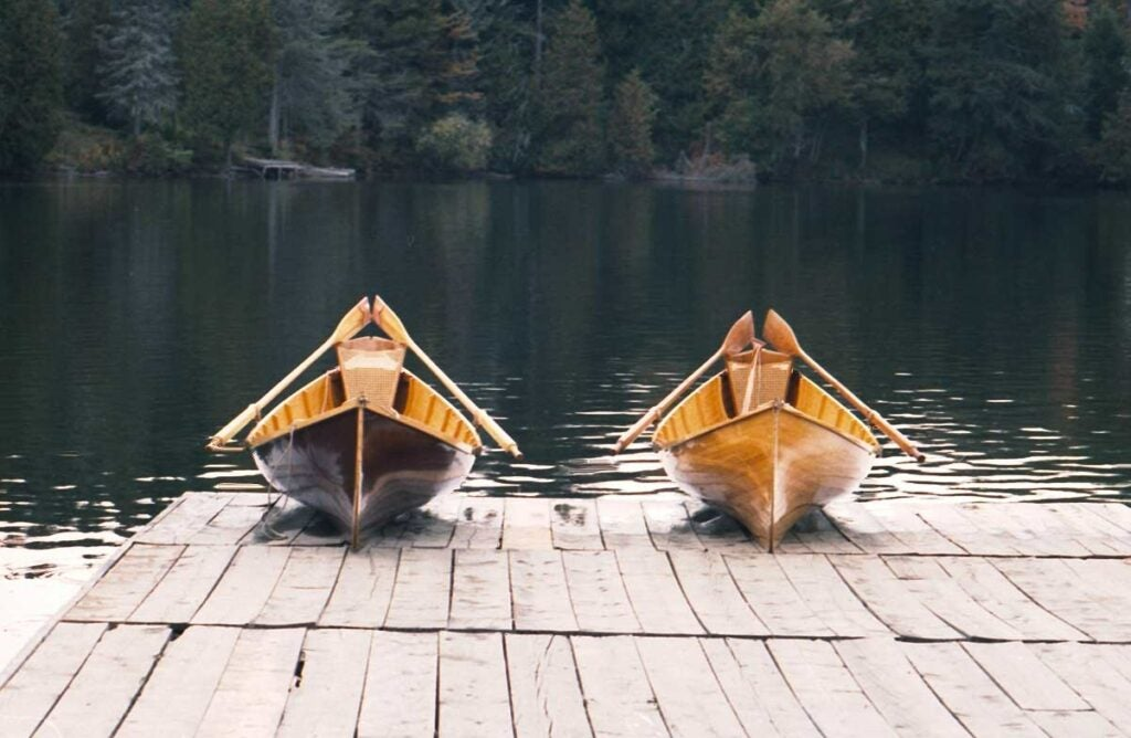 Two Adirondack guide boats sit ready on a dock.