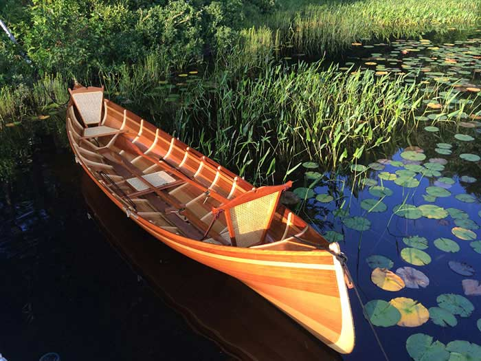 A cedar Adirondack guide boat floats on a bed of lily pads.