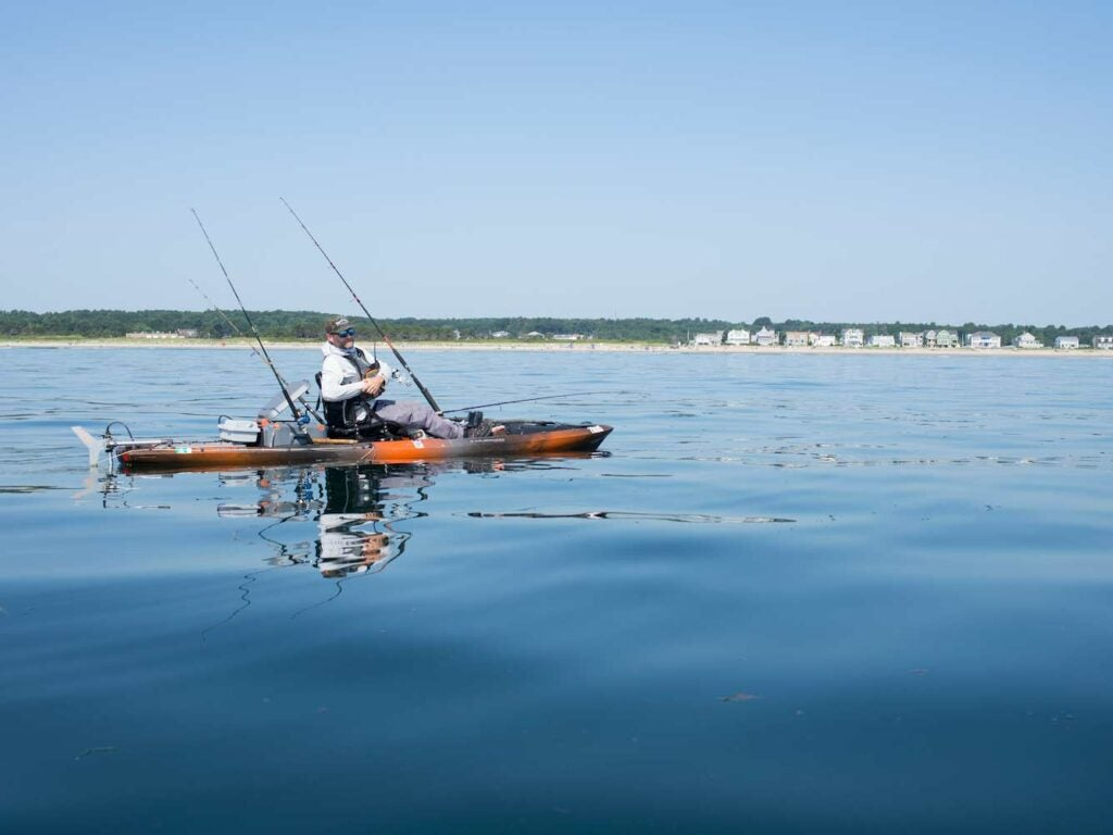 A fishing kayak with a motor attached to the stern glides across the water.