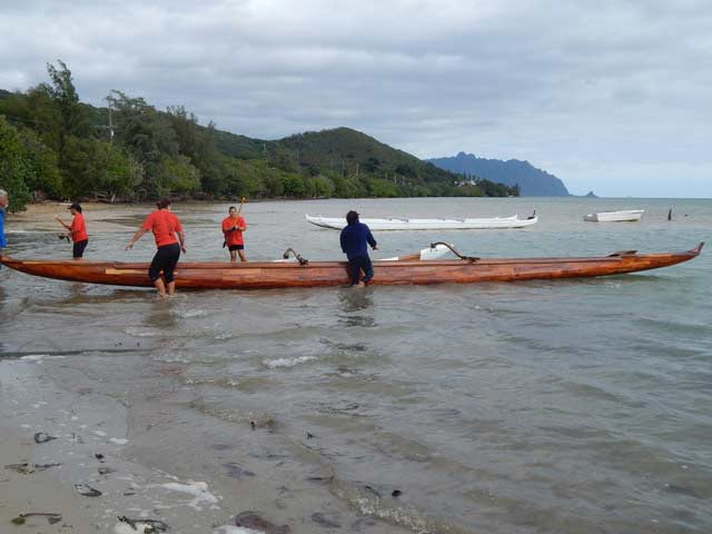A team prepares to paddle a traditional wooden koa canoe.