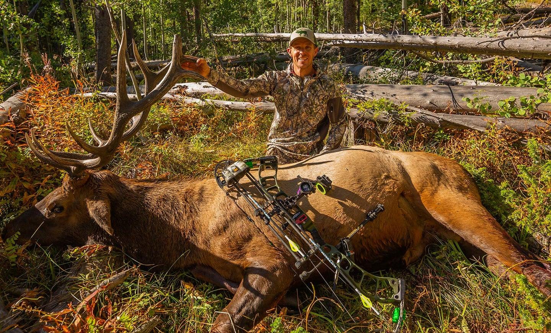elk hunter kneeling behind giant elk