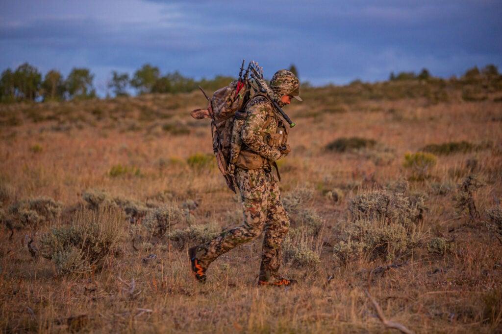 hunter walking through a barren desert field