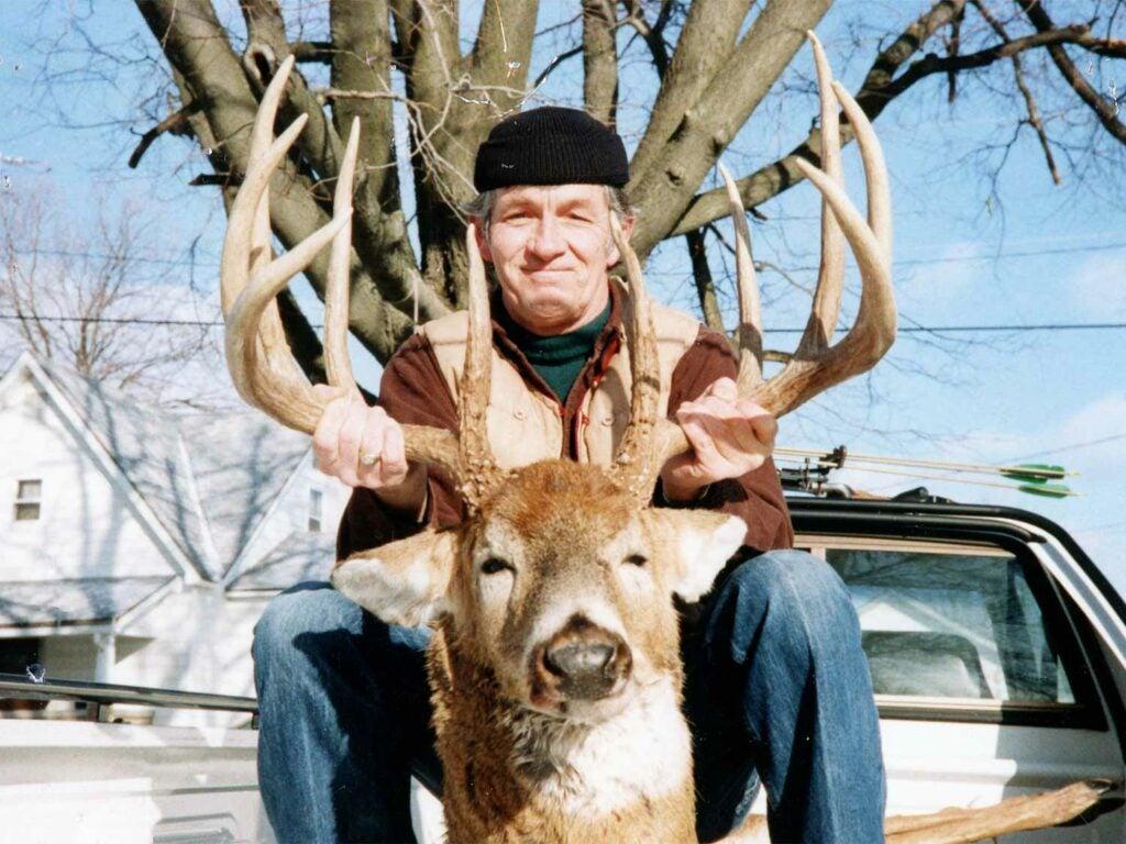 hunter with giant antlered indiana buck