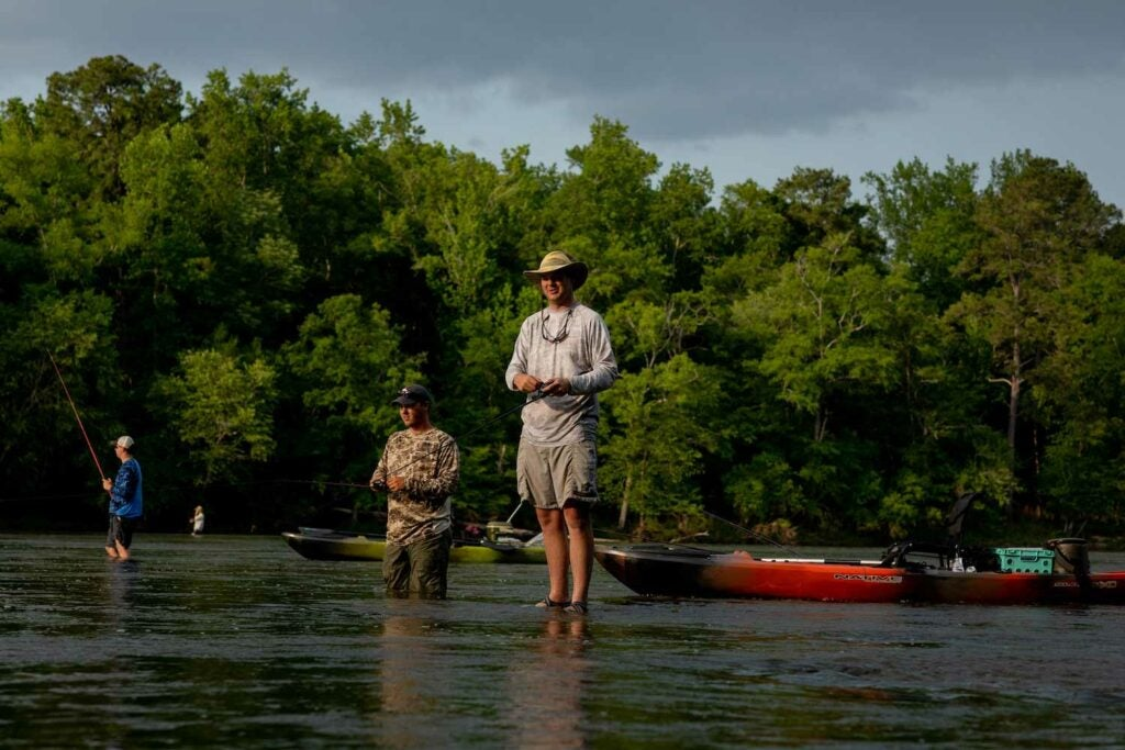 Anglers cast soft plastics into the current for shoal bass.