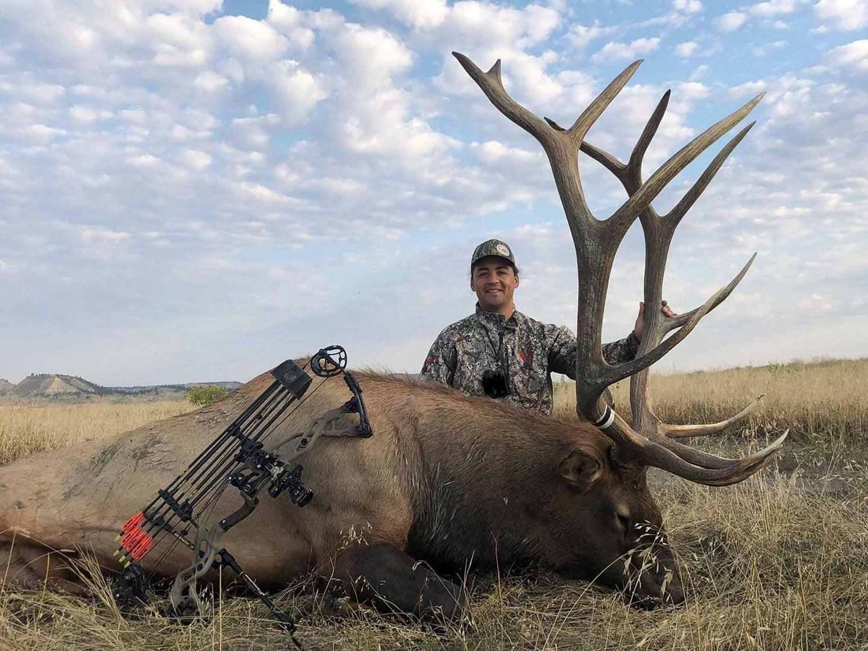Yahsti Perkinskiller kneeling behind a giant bull elk