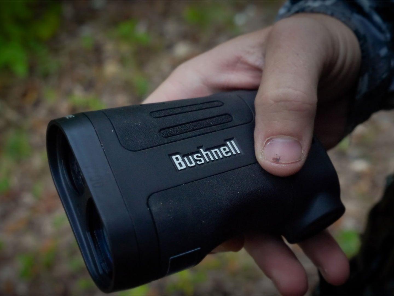 hand holding a bushnell rangefinder