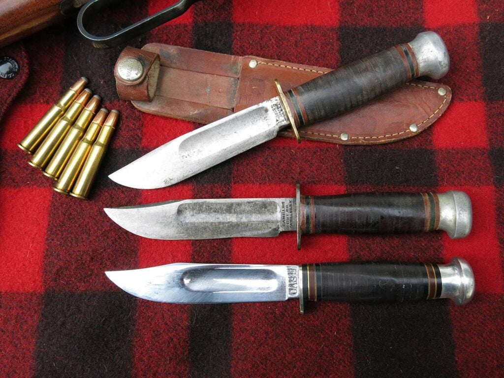 three antique hunting knives on a plaid backdrop