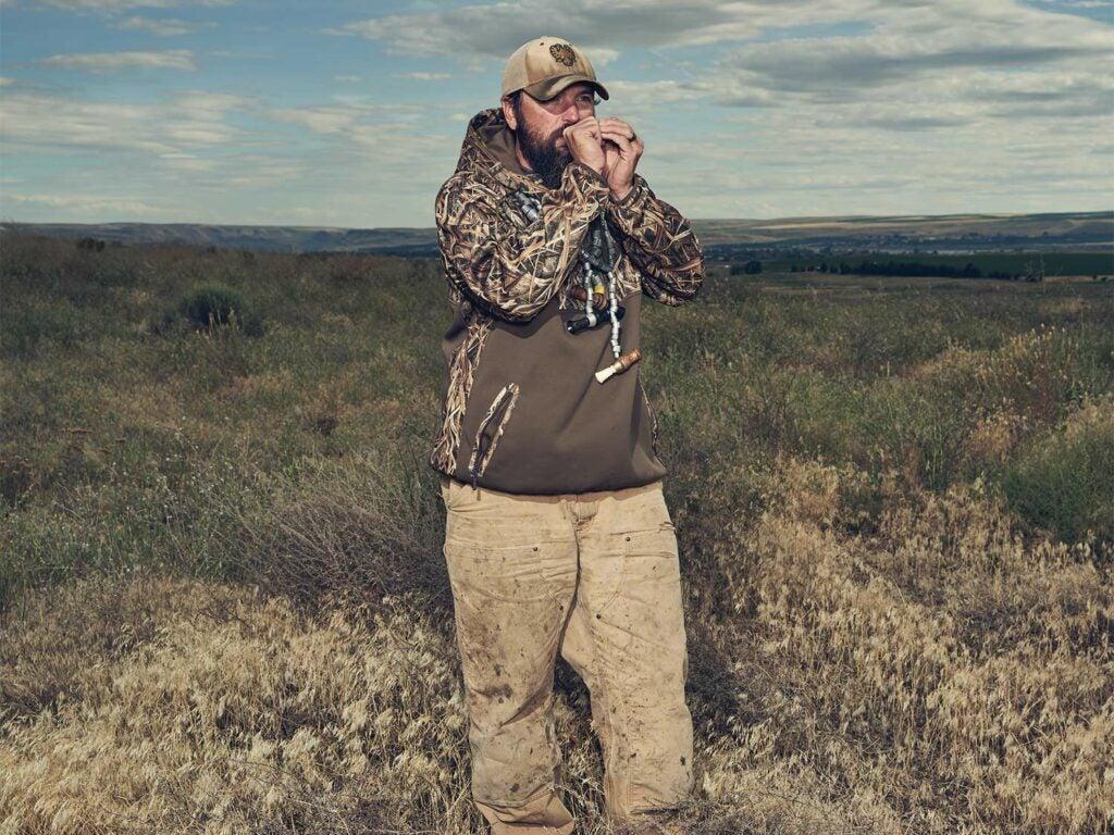 a hunter standing in a field calling ducks