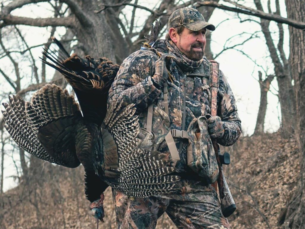 turkey hunter with a turkey over the shoulder