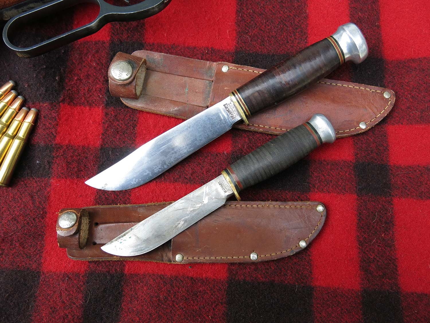 two hunting knives and sheathes