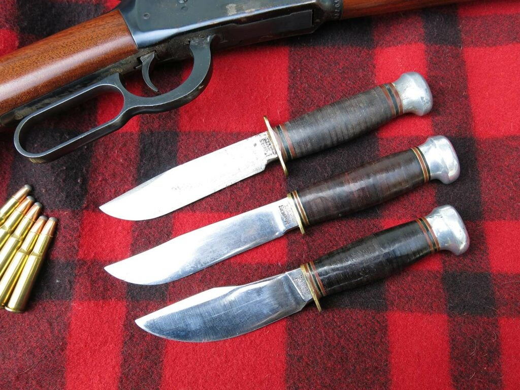 three hunting knives and a lever-action rifle