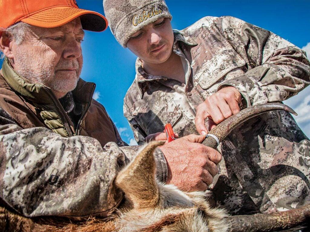 hunter and sun measuring antler horns