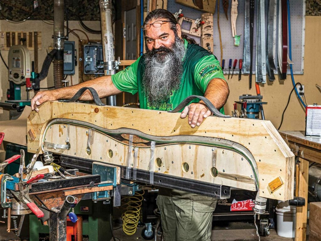 hunter shaping a recurve bow