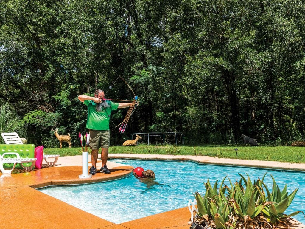 man testing a custom crafted bow by a pool