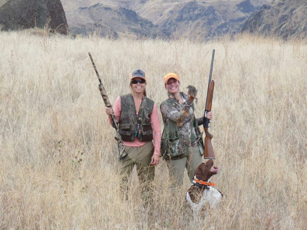 two women hunting chukar in a field