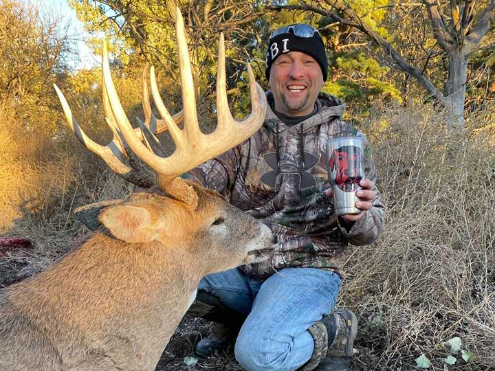 David Shelby kneeling behind a whitetail buck.