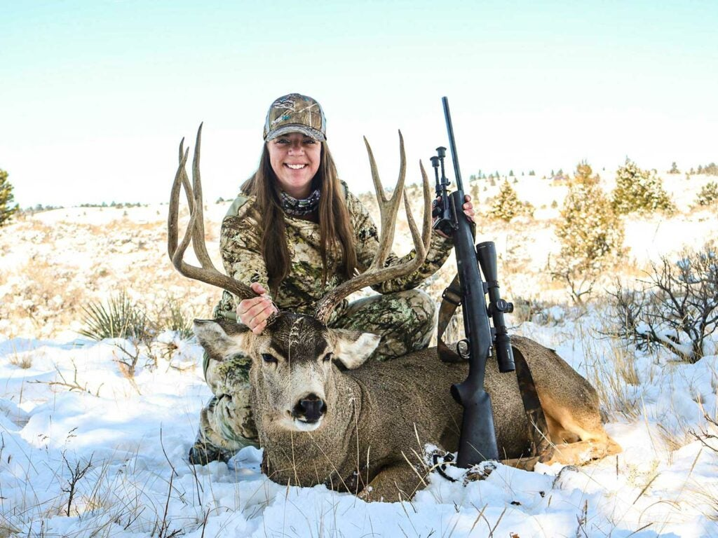 Erika Meister with a whitetail buck in the snow.